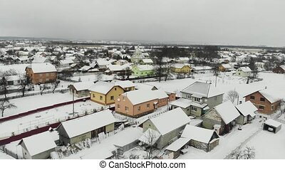 horizontal view of snowy roofs in village. winter weather.