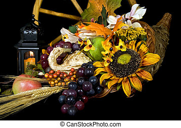 Horn Of Plenty - Cornucopia with candle on black background.