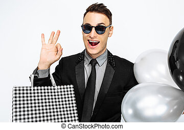 Horny guy in black suit and sunglasses, with bags and balloons, shows good gesture and class, and waits for black Friday, on white background. Black Friday