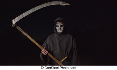 Spooky grim reaper in black cloak walking on country road in darkness, frightening with scythe, expressing ruthlessness, fear and horror while haunting for souls of deceased on halloween.