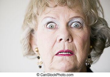 Horrified Senior Woman - Close-up of a senior woman with a...