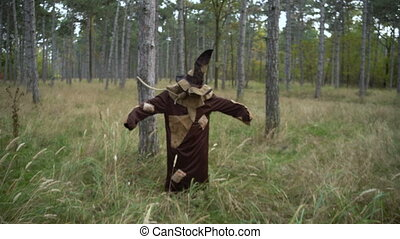 Horror bonded Scarecrow standing in the forest with Sackcloth Mask