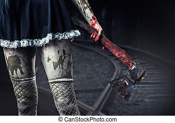 Horror. Dirty woman's hand holding a bloody axe outdoor in night forest