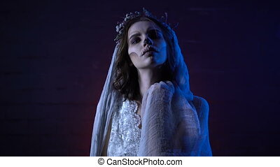 Horror halloween scene of a corpse bride with sad face and sewed mouth looking at the camera the dark background. Young girl scary make-up rising her hands trying to touch the