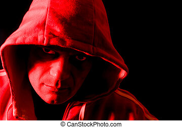 Horror portrait of a hooded man, lit by a red strobe from the side.
