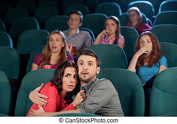 Horror movie. Terrified young couple hugging while watching movie at the cinema