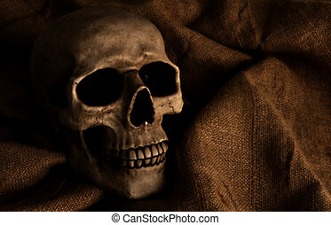 Horror - Scary dimly lit human skull laying on the gunny...
