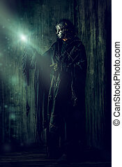 horror - Scary man in iron mask and black robe. Fantasy....