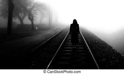 Horror movie scene of woman in black dress staying at the rail tracks.