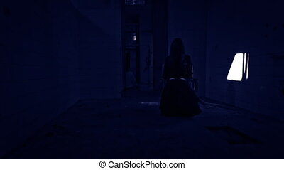 Horror movie sequence. Woman sitting on a chair. Thunderstorm.