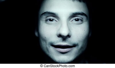 Horror scene with screaming scary human face with a harsh light on a black background - Halloween concept with young man with open mouth and teeth