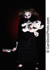 Horror shot: evil demonic girl with torn rabbit toy and bloody knife in hands
