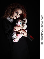 Horror shot: sad gothic girl with rabbit toy and bloody knife in hands