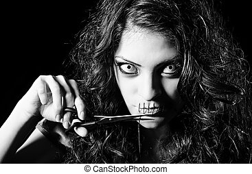 Horror shot: scary strange girl with mouth sewn shut cutting...