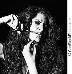 Horror shot: strange girl with mouth sewn shut cutting the...