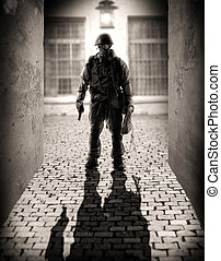 Horror. silhouette of a dangerous military men holding hand gun in the alley by the light of a lantern at night