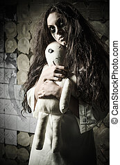 Horror style shot: strange sad girl with moppet doll in hands