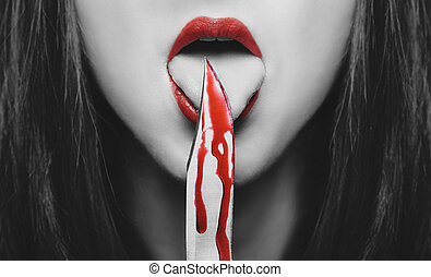Horror woman with knife - Dangerous young woman licking a...