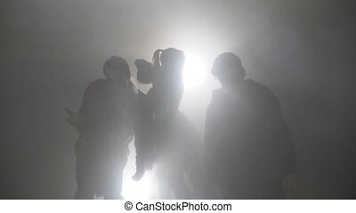 Horror zombie friends males and female dancing in foggy...