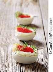 Boiled egg whites filled with red caviar