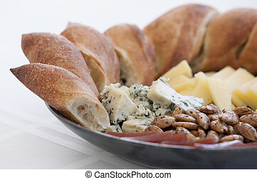 Bread, Roquefort cheese, gruyère cheese, almonds and prociutto served on a grey ceramic plate as hors d'oeuvres