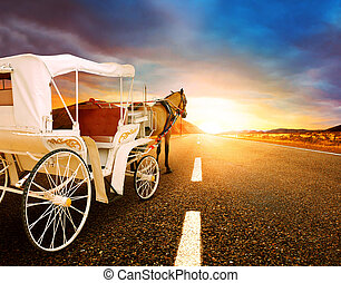 horse and classic fairy tale carriage on asphalt road perspective to beautiful land scape with sun rising sky