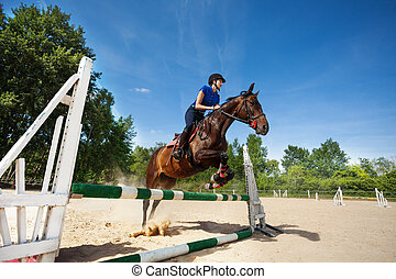 Horse and female jockey jumping over barrier