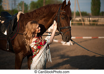 Horse and woman in a scarf on the ranch