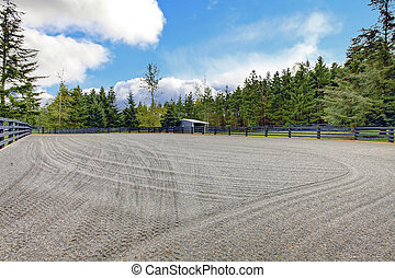 Horse farm riding open arena with gravel.