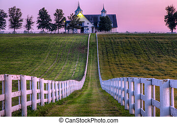 White fences in front of a stable at a horse farm in Kentucky at sunset