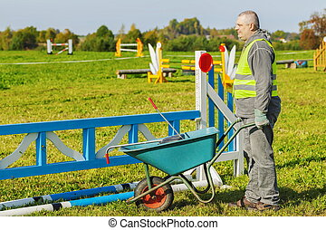 Horse handler with wheelbarrow