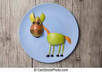Horse made with apple and pear on plate and wooden texture