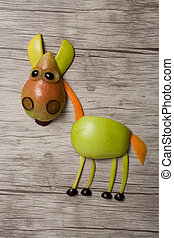 Horse made with apple and pear on wooden background