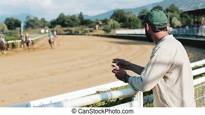 Horse racing. Enthusiast of spectator at horse racing. The man bet on a horse. The bookmaker wins with a smartphone in his hands