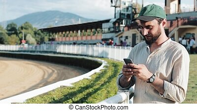 Horse racing. The man bet on a horse with a smartphone....