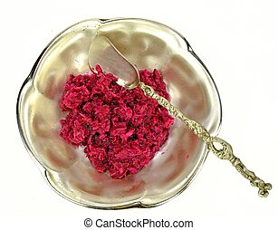 Horse radish in a metal bowl with a spoon on a white background.
