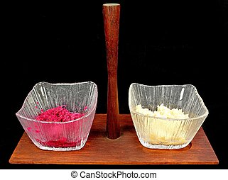 Horse radish in glass bowls on a black background.