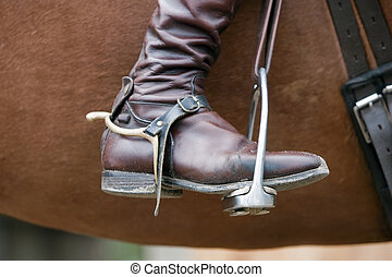 Old-fashioned brown leather riding boot in a stirrup
