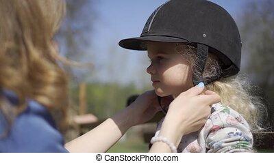 Horse riding girl child helmet. Gimbal motion shot - Horse...