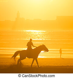 Horse riding on the beach at sunset.