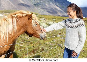 Horse - woman petting Icelandic horses in sweater