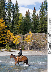 Horseback Rider - Cowboy on his horse crossing a river in...