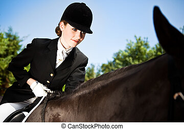 A caucasian teenage girl riding a horse outdoor