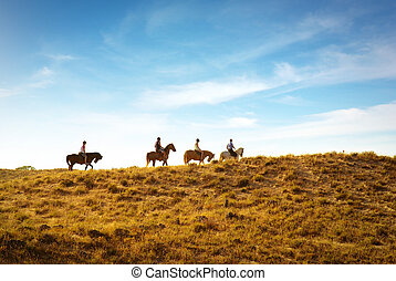 horseback riding in the dunes near a beach at sunset