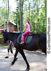 Horseback riding little girl