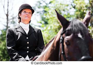 Horseback riding senior woman