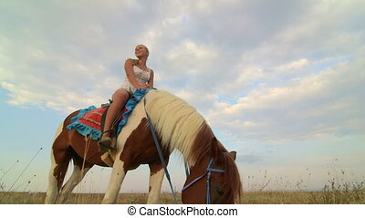 Horseback riding vacations girl rider with her horse in the field