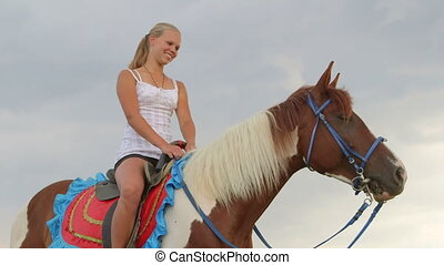 Horseback riding vacations young girl smiling in saddle...