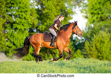 Young woman is riding a horse in summertime
