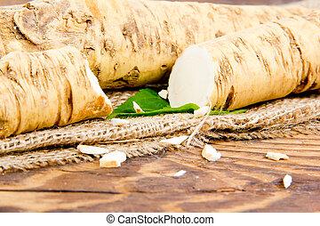 Horseradish - Photo of horseradish root with slice on burlap...